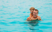 The happy child swimming with the father in the tropical resort in the sea — Stock Photo