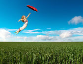 Flying girl with red umbrella — Stock Photo