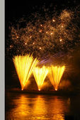 Gold color fireworks above the river — Stock Photo