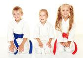 Wesoły młodych sportowców w kimono, siedząc w karate stanowią rytuał — Zdjęcie stockowe