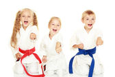 Young children with a smile in kimono sitting in a ritual pose karate punch arm — Stock Photo