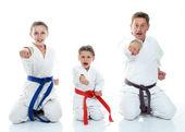 Vater mit zwei Töchtern sitzen in einem Ritual darstellen Karate und seine Faust schlagen — Stockfoto