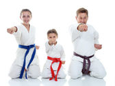 Dad and his daughters sitting in a ritual pose karate and beat his fist — Stock Photo