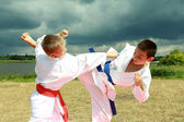 In the kimono two athletes are hitting arm and leg on the background stormy sky — Stock Photo