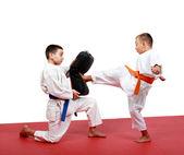 Boy v kimonu hity nohy kop simulátor který v rukou jiné sportovce — Stock fotografie