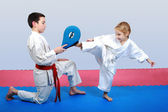 Little girl with a white belt beat leg on the simulator in the hands of a boy with a red beltLittle girl with a white belt beat leg on the simulator in the hands of a boy with a red belt — Stock Photo
