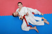 Two young athlete with a red and white belt show finger super — Stock Photo