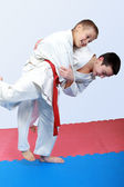 Athletes with a white and red sash do judo throw — Stock Photo