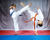 Blows legs to meet each other are beating athletes in karategi — Stock Photo