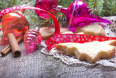 Christmas decorations and cookies over wooden background — Stock Photo