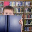 Boy with Blue Book in Library — Stock Photo #18052915