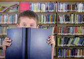 Garçon avec le livre bleu en bibliothèque — Photo
