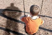 Vyděšený chlapec na swingset s vlivné obranných — Stock fotografie