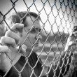 Stock Photo: Upset Man Holding Chain Fence Barrier