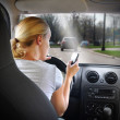 Stock Photo: WomTexting on Phone and Driving Car