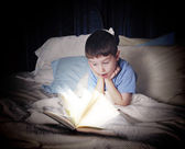 Child Reading Open Book at Night in Bed — Stockfoto