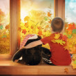 Little Child Watching Fall Leaves in Window — Stock Photo