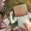 Flying Books Around Sleeping Boy in Grass — Foto de Stock