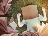 Flying Books Around Sleeping Boy in Grass — Stock Photo