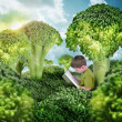 Healthy Child Reading Book in Green Broccoli Landscape — Stock Photo #45919599