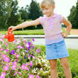 Girl watering flowers — Stock Photo