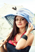 Young lady in hat with an umbrella — Stock Photo