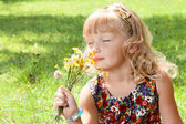 Little girl enjoys the smell of flowers — Stock Photo