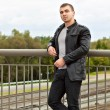 Brutal young sexual man in a leather jacket - Stock Photo