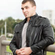 Brutal young man in a leather jacket - Stock Photo