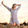 Beautiful woman walking on wheat field — Stock Photo
