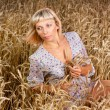 Beautiful woman sitting on wheat field - Stock Photo