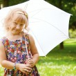 Girl under umbrella in the park - Stock Photo