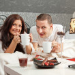 Breakfast on a table with couple lying — Stock Photo #15634773