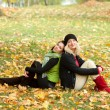 Two young women sitting in autumn park — Stock Photo