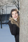 Beautiful girl looking beyond the tree — Stock Photo
