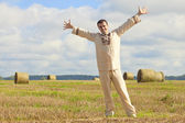 Carefree man standing in golden wheat — Stock Photo