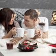 Breakfast on a table with couple lying — Stock Photo #19633169