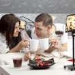 Breakfast on a table with couple lying — Stock Photo