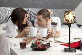 Breakfast on a table with couple lying — Foto Stock