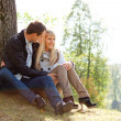 Young loving couple sitting on ground by tree — Stock Photo