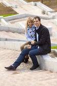Happy young couple sitting on stairs — Stock Photo