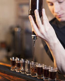 Bartender fills a few glasses in a row — Stock Photo