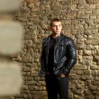 Brutal young sexual man in a leather jacket — Stock Photo #22789266