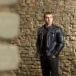 Brutal young sexual man in a leather jacket — Stock Photo