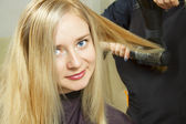 Hairdressers hands drying long blond hair — Stock Photo