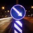Direction indicator and light trails - Stock Photo