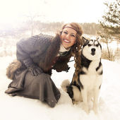 Happy young woman sitting with siberian husky dog — Stock Photo