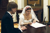 The bride and groom sign the marriage contract — Stock Photo