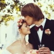 Beautiful groom kissing young bride — Stock Photo