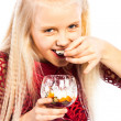 Beautiful blonde girl eating dessert - Stock Photo